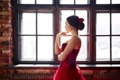 Stående av en härlig dansare för ung kvinna i en röd klänning nära fönstret royaltyfria foton