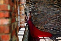 Stående av en härlig dansare för ung kvinna i en röd klänning nära fönstret arkivfoton