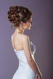 Stående av en härlig försiktig och elegant flickakvinnabrud i en vit klänning med en härlig frisyr och makeup Royaltyfri Fotografi