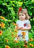 Stående av en härlig flicka bland blommorna Arkivbild