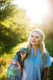 Stående av en härlig flicka i en blå klänning med en huvudvärk i ett fält på solnedgången i sommar Tillfällig sommarkläder Närbil royaltyfri bild