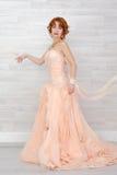 Stående av en härlig flicka i en beige persikaklänning Royaltyfria Bilder