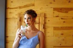 Stående av en härlig flicka i en cofee med ett exponeringsglas av cappuccino Royaltyfria Foton