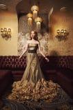 Stående av en härlig flicka i en guld- klänning i härlig inre royaltyfri foto