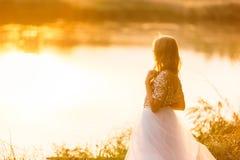Stående av en härlig flicka i en klänning på solnedgången nära en sjö arkivfoto