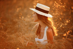 Stående av en härlig flicka i en vit klänning och hatt i fien arkivfoto