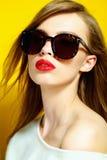 Stående av en härlig flicka i exponeringsglas på en gul bakgrund i studion Royaltyfri Foto