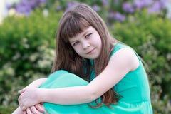 Stående av en härlig flicka i en grön klänning Arkivfoto