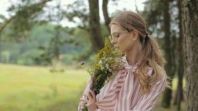Stående av en härlig flicka i intressant klänning- och exponeringsglasposion till kameran stock video