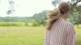 Stående av en härlig flicka i intressant klänning- och exponeringsglasposion till kameran lager videofilmer