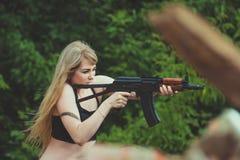 Stående av en härlig flicka i kamouflage i hennes armar under a royaltyfria bilder