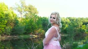 Stående av en härlig flicka i en rosa klänning nära en flod med makeup på solnedgången i sommar stock video