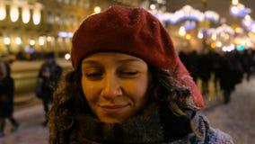Stående av en härlig flicka i vintern i nattstaden folkmassor av folk och bilar i bakgrunden arkivfilmer