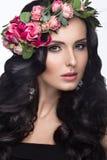 Stående av en härlig flicka med ett försiktigt smink och massor av blommor i hennes hår Spring avbildar Härlig le flicka Arkivfoton