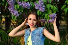 Stående av en härlig flicka med lila blommor royaltyfria foton