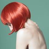 Stående av en härlig flicka med rött kort hår i studion på en grön bakgrund Royaltyfri Fotografi