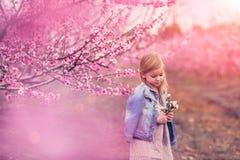 Stående av en härlig flicka nära ett blomningträd av mandlar och lilor arkivfoto