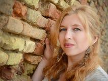 Stående av en härlig flicka nära tegelstenväggen Royaltyfria Bilder