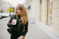 Stående av en härlig flicka på gatan som rymmer en pappers- kopp Arkivbilder