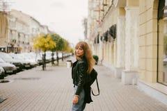 Stående av en härlig flicka på gatan som rymmer en pappers- kopp Arkivfoto