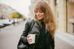 Stående av en härlig flicka på gatan som rymmer en pappers- kopp Royaltyfria Foton