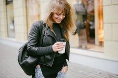 Stående av en härlig flicka på gatan som rymmer en pappers- kopp Royaltyfri Fotografi