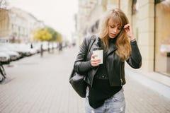 Stående av en härlig flicka på gatan som rymmer en pappers- kopp Royaltyfri Foto