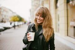 Stående av en härlig flicka på gatan som rymmer en pappers- kopp Arkivbild