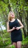 Stående av en härlig flicka på naturen, i träna, i en svart klänning. Arkivfoto