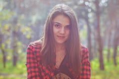 stående av en härlig flicka som bär en plädskjorta på bakgrunden av höstskogen royaltyfria foton