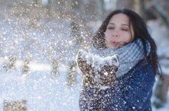 Stående av en härlig flicka som blåser snöflingorna från hennes händer Fotografering för Bildbyråer