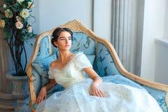Stående av en härlig flicka som läser en bok på en soffa i en härlig klänning arkivbilder