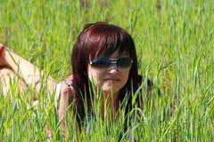 Stående av en härlig flicka som ligger på gräset Fotografering för Bildbyråer
