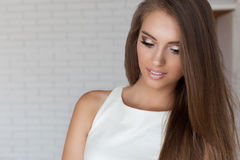 Stående av en härlig gullig försiktig härlig ung flicka med snövitt leende med ljus makeup i en vit märkes- klänning Arkivbild