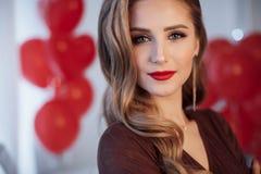 Stående av en härlig kvinna i dag för valentin` s på en bakgrund av röda luftballonger arkivfoton