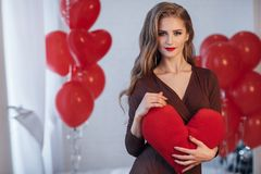 Stående av en härlig kvinna i dag för valentin` s på en bakgrund av röda luftballonger arkivfoto