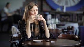 Stående av en härlig kvinna i ett kafé eller en restaurang En flicka dricker te eller kaffe och drömmer om något arkivfilmer