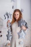 Stående av en härlig kvinna i inre med jul december Arkivfoto