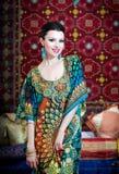 Stående av en härlig kvinna i orientalisk klänning Nåd och skönhet Arkivbild