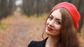Stående av en härlig kvinna i en röd basker och med röda kanter, som ler och ser in i den utomhus- kameran stock video