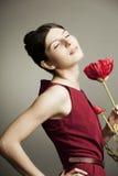 Stående av en härlig kvinna med en blomma Arkivbild