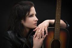 Stående av en härlig kvinna med en gitarr Royaltyfri Foto