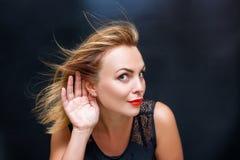 Stående av en härlig kvinna med en hand nära hennes öra arkivfoton
