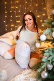 Stående av en härlig kvinna nära gulligt le för julgran royaltyfri fotografi
