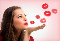 Stående av en härlig kvinna som blåser röda kyssar Royaltyfria Bilder