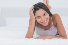Stående av en härlig kvinna som kopplar av att ligga i säng Arkivfoto