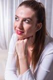 Stående av en härlig kvinna som ler in i ljuset Arkivfoto