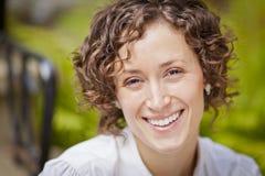 Stående av en härlig kvinna som ler på kameran arkivfoto