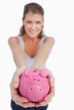 Stående av en härlig kvinna som visar en piggy grupp Fotografering för Bildbyråer
