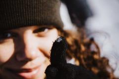 Stående av en härlig kvinna som visar en snöflinga på hennes fingerspets Arkivbilder